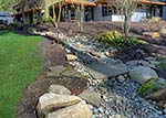 river rock drainage with flagstone bridge